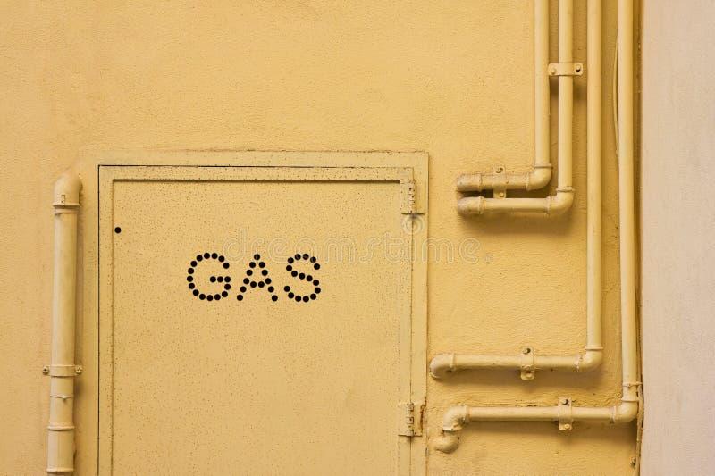 De oude pijpen van het gasmetaal vast met steunen voor een pleistermuur met metaaldoos voor watermeter royalty-vrije stock afbeelding