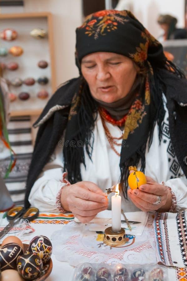 De oude pysankar vrouw schrijft een bloemen volksornament op paaseipysanka, Vinnytsia, de Oekraïne, 19 03 2018 royalty-vrije stock foto's