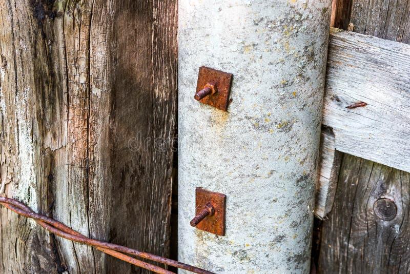 De oude raad wordt vastgemaakt met roestige bouten met noten en wasmachines aan de concrete pijler stock foto's