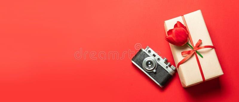 De oude retro uitstekende camera, giftvakje met rood lint op rode achtergrond hoogste meningsvlakte legt met exemplaarruimte royalty-vrije stock afbeeldingen