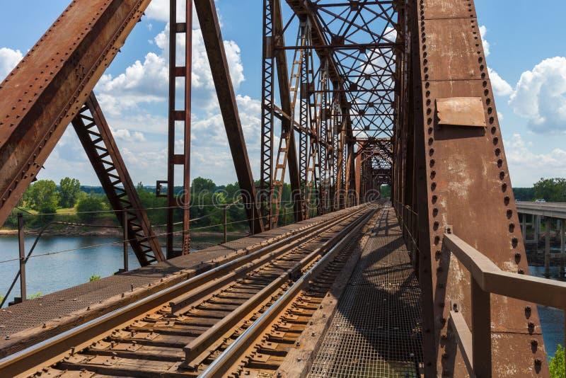 De oude roestige brug van de bundelspoorweg over de Rode Rivier op de grens royalty-vrije stock foto's