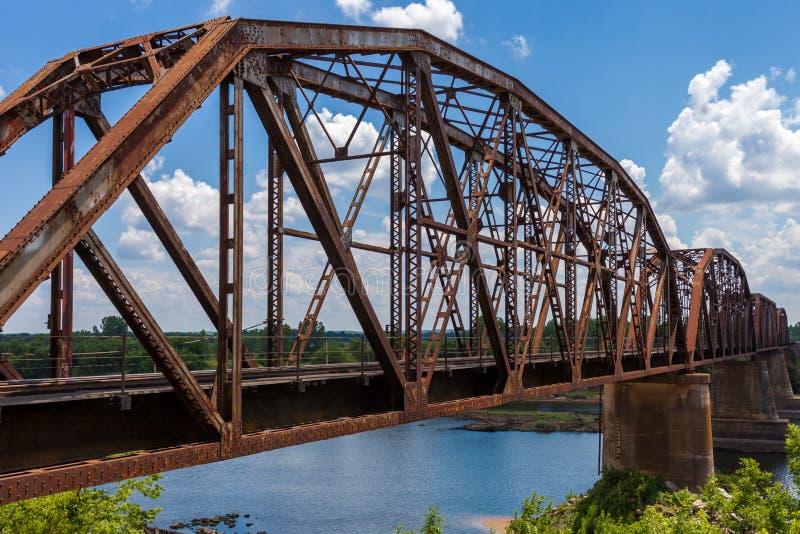 De oude roestige brug van de bundelspoorweg over de Rode Rivier op de grens royalty-vrije stock fotografie