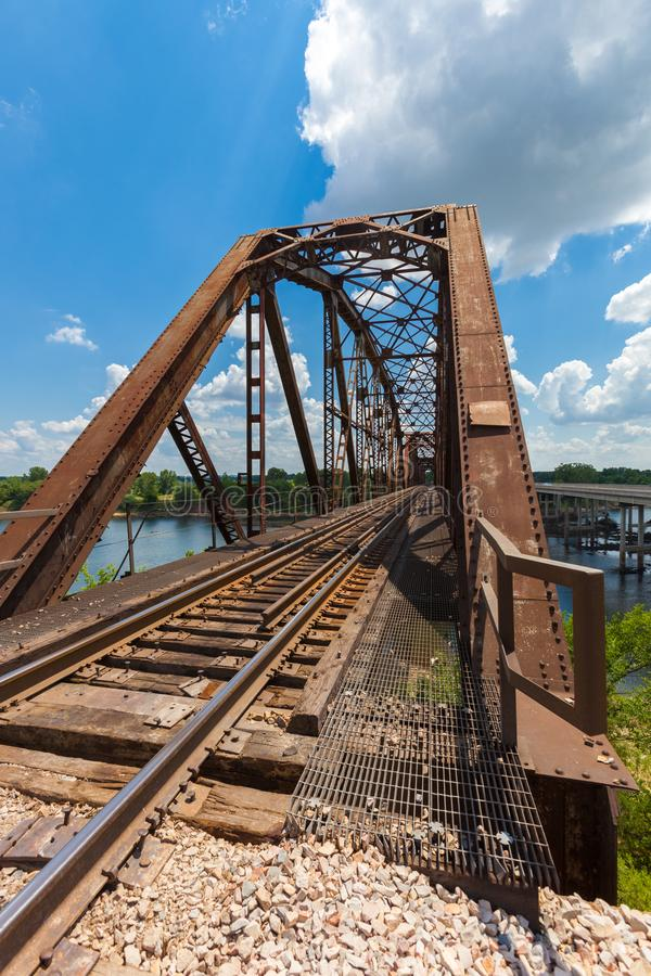 De oude roestige brug van de bundelspoorweg over de Rode Rivier op de grens stock foto