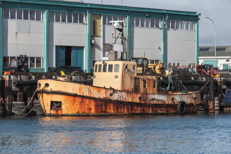 De oude roestige die tribunes van de sleepbootboot in haven worden vastgelegd stock fotografie