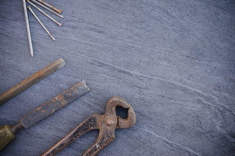 De oude roestige hulpmiddelen en de spijkers van het handtimmerwerk op een houten lijst Uitstekende buigtang royalty-vrije stock foto