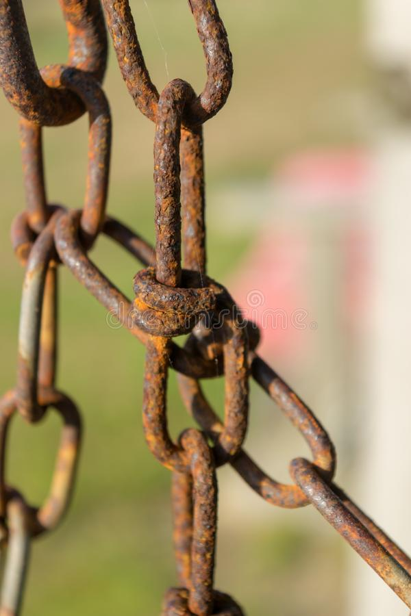De oude roestige ketting en de ketting verbinden, tegen een natuurlijke groene bokehachtergrond, close-up, Blokeiland, RI stock foto