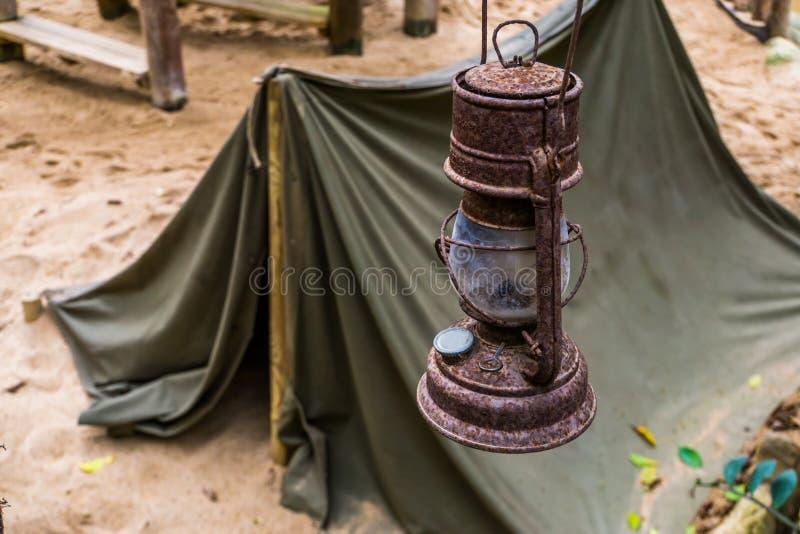 De oude roestige lantaarn met een tent op de achtergrond, de Mijnwerkers kampeert, overlevingsstijging in aard royalty-vrije stock fotografie