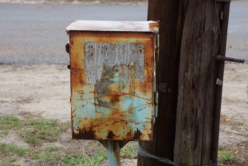 De oude roestige metaaldoos voor elektriciteit is op de straat stock fotografie
