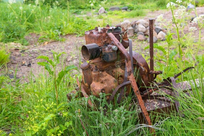 De oude roestige motor van een auto bevindt zich in het gras royalty-vrije stock fotografie