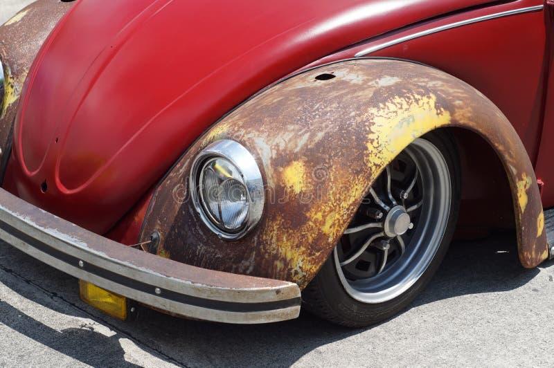 De oude roestige rode die auto van VW Volkswagen voor restauratie in openbaar parkeerterrein wordt bekeken stock foto's