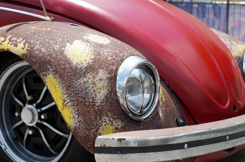 De oude roestige rode die auto van VW Volkswagen voor restauratie in openbaar parkeerterrein wordt bekeken royalty-vrije stock afbeeldingen