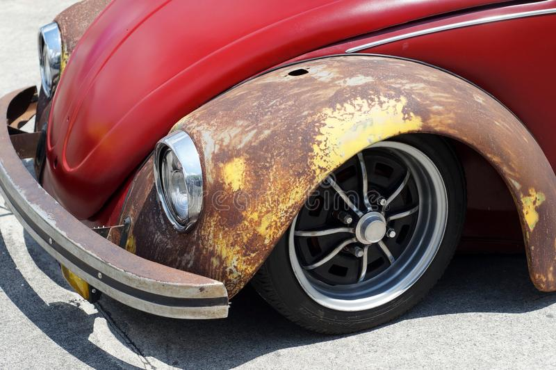 De oude roestige rode die auto van VW Volkswagen voor restauratie in openbaar parkeerterrein wordt bekeken stock fotografie