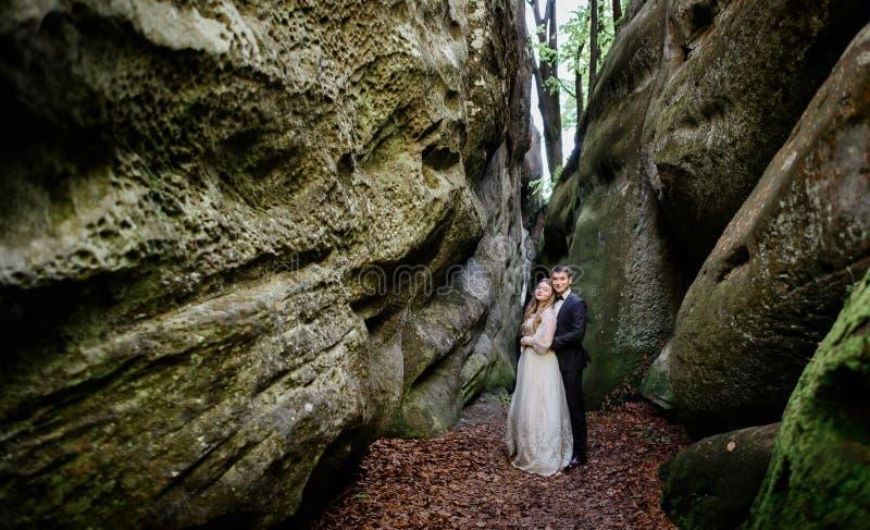 De oude rotsen hingen over het dromerige huwelijkspaar royalty-vrije stock fotografie
