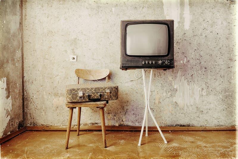 De oude ruimte met retro TV, een stoel en een koffer royalty-vrije stock afbeelding
