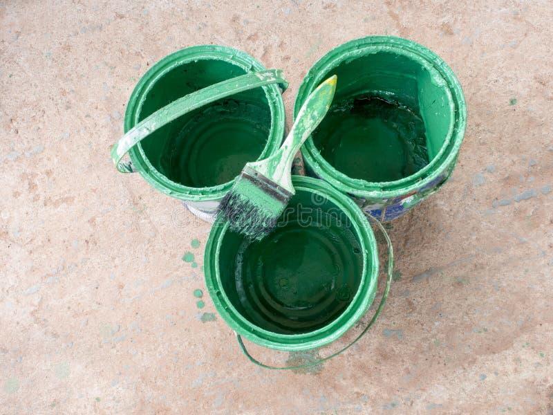 De oude rust van de verfborstel bovenop groene verfemmer royalty-vrije stock fotografie