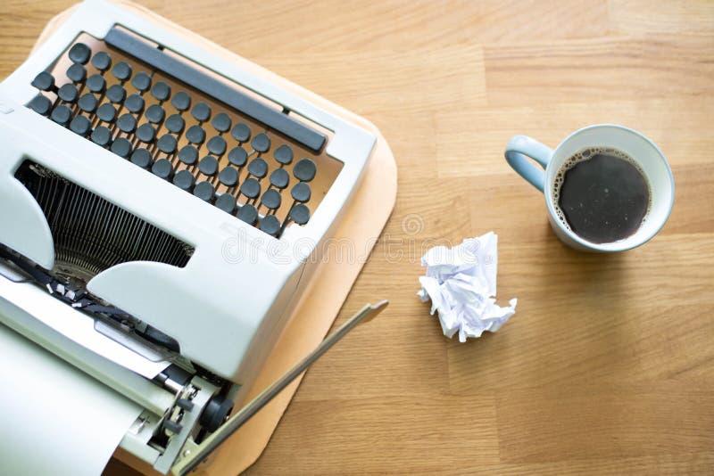 De oude schrijfmachine Wij drukken een boek in een kat en een koffiebedrijf royalty-vrije stock afbeeldingen
