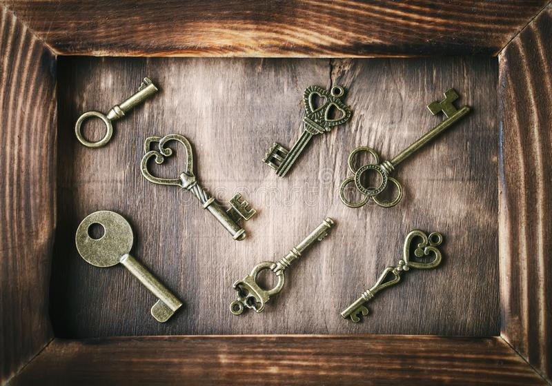 De oude sleutels liggen op een houten lijst stock fotografie
