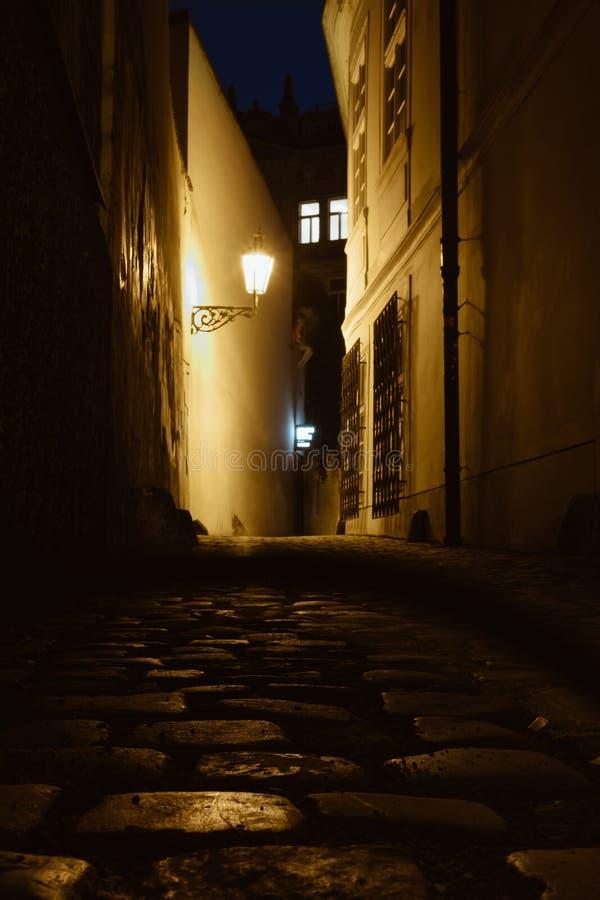 De oude smalle straat van Praag met oude straatstenenweg twiligh stock afbeelding