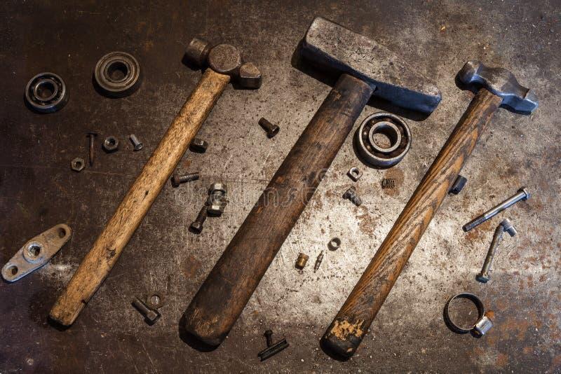 De oude staalhamers met houten handvatten en sommige bouten, noten, lagers, kleppen, wasmachines, spijkers op de metaalachtergron stock afbeelding