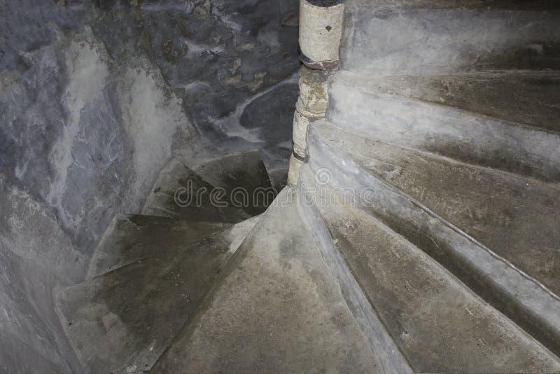 De oude, steenachtige wenteltrap, een kasteel of een vesting, daalt in griezelige dark royalty-vrije stock foto's