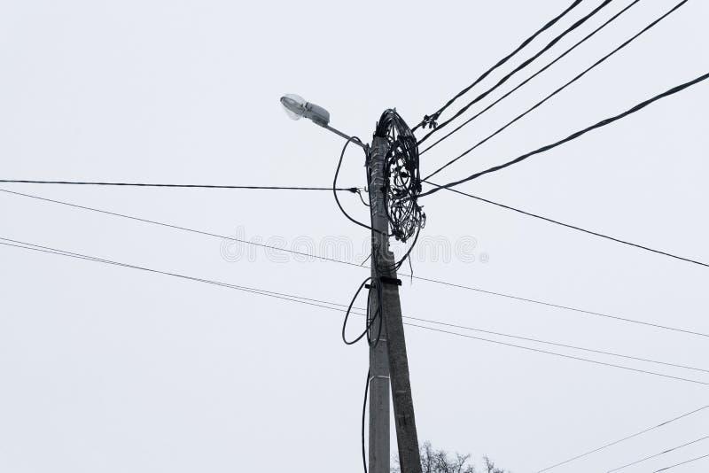 De oude straatlantaarn met vele kabels verbond, geïsoleerd op grijze hemel De ruimte van het exemplaar royalty-vrije stock foto's