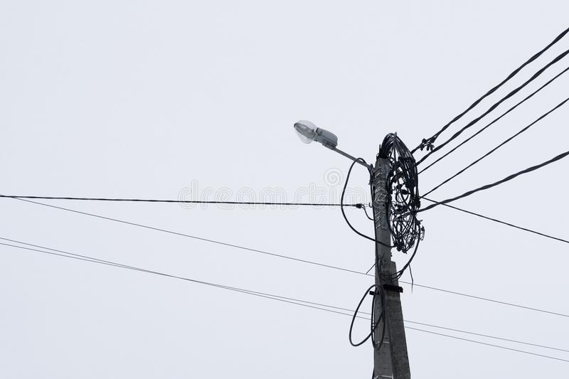 De oude straatlantaarn met vele kabels verbond, geïsoleerd op grijze hemel De ruimte van het exemplaar royalty-vrije stock foto