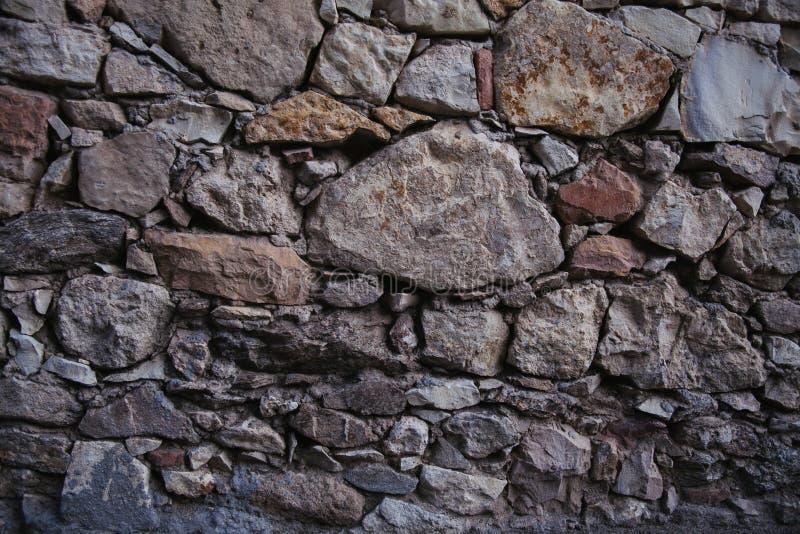 De de oude textuur en achtergrond van de steenmuur De achtergrond van de rotsmuur stock afbeeldingen