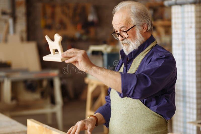 De oude timmerman is met klaar het maken van houten stuk speelgoed stock afbeelding