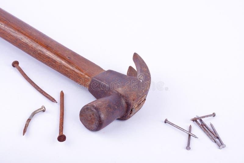 de oude Traditionele gebogen die klauwhamer en de roest nagelen kopspijker op wit geïsoleerd hulpmiddel wordt gebruikt als achter stock foto