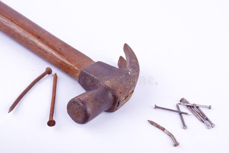 de oude Traditionele gebogen die klauwhamer en de roest nagelen kopspijker op wit geïsoleerd hulpmiddel wordt gebruikt als achter stock afbeelding