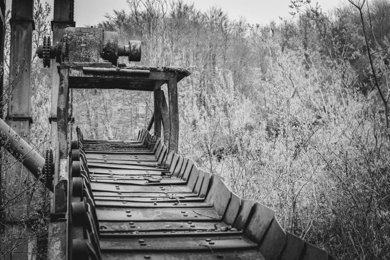 De oude transportband van de mijnbouwfabriek in aard stock foto's