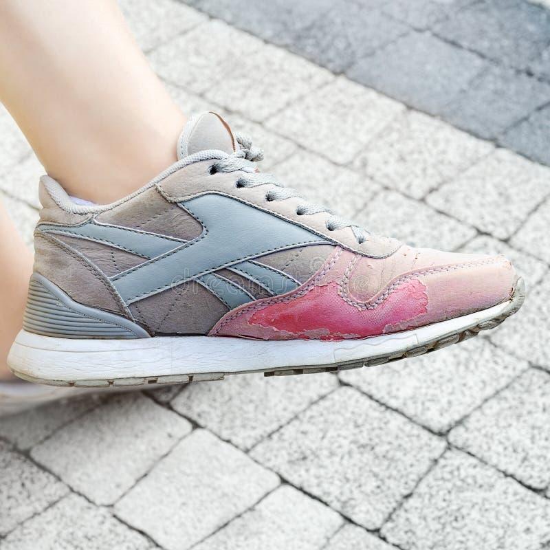 De oude uitgeputte tennisschoenen op mijn comfortabele voeten, en het is een medelijden aan wegwerp Kazan, Rusland 24 Juni 2019 stock foto's
