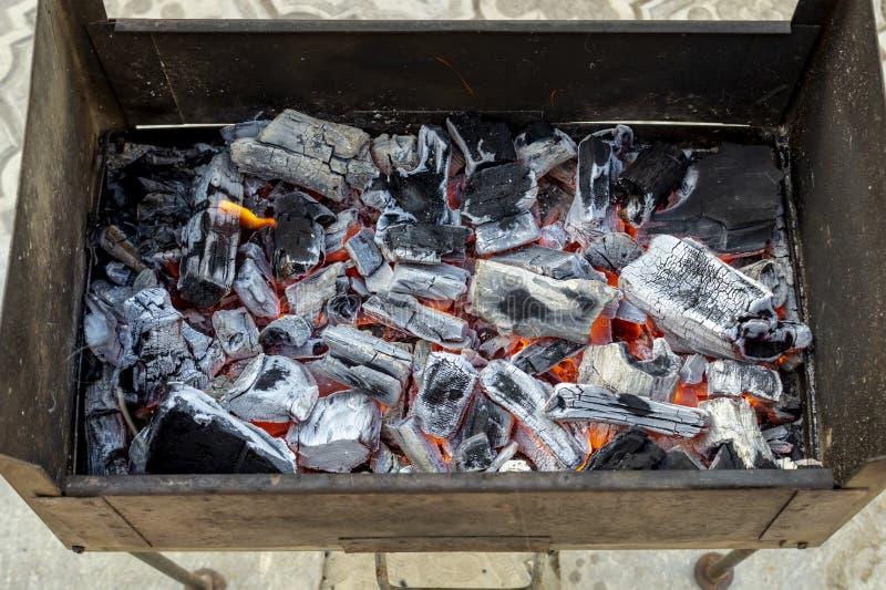 De oude uitstekende metaalkoperslager met hete steenkolen Close-up van smeulende as van vuur Brandende steenkolen voor een kebab royalty-vrije stock foto's