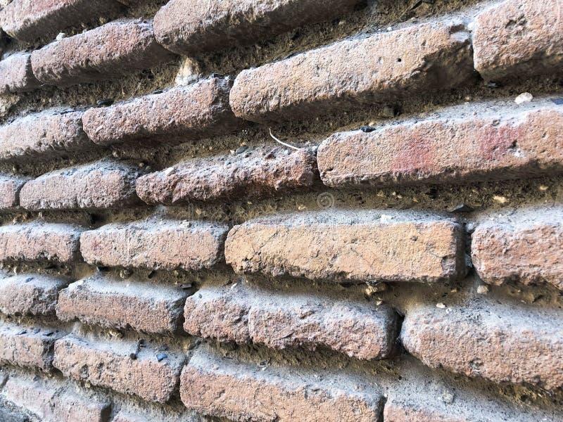 De oude uitstekende middeleeuwse middeleeuwse stoffige authentieke bruine baksteen van de texturensteen met naden op een bakstene stock afbeelding