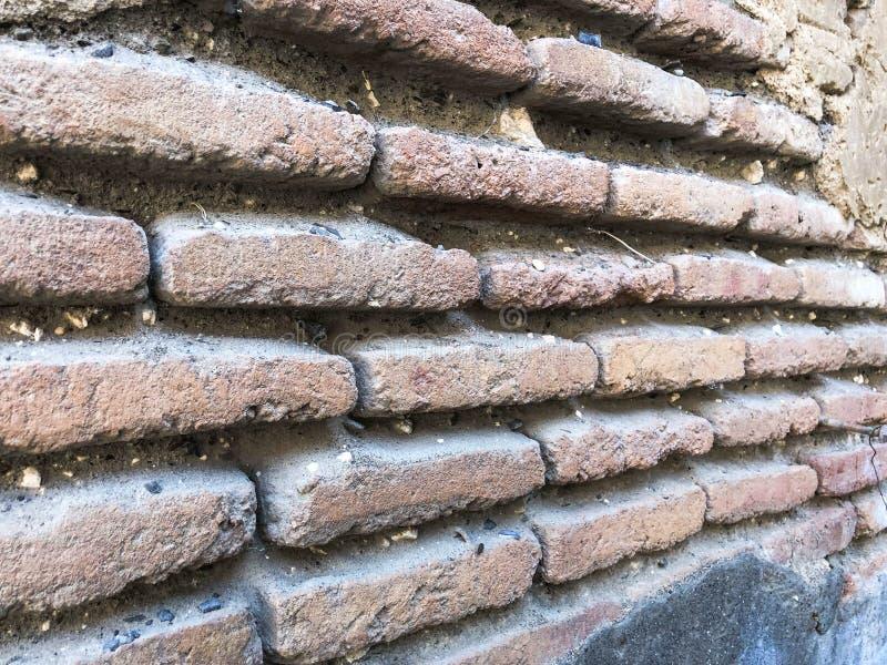 De oude uitstekende middeleeuwse middeleeuwse stoffige authentieke bruine baksteen van de texturensteen met naden op een bakstene royalty-vrije stock afbeeldingen