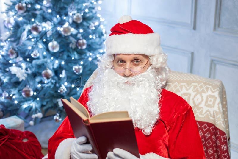 De oude Vader Christmas ontspant als zijn voorzitter stock foto