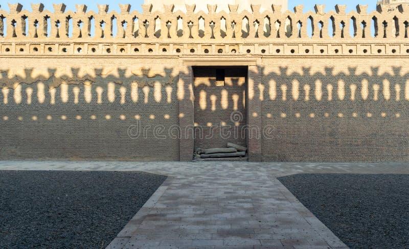 De oude verfraaide omheining van steenbakstenen met houten deur en schaduwen van decoratie van de tegenovergestelde omheining, Mo stock fotografie