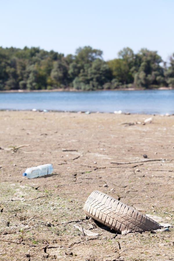 De oude verlaten autoband ligt op de rivierbank stock foto