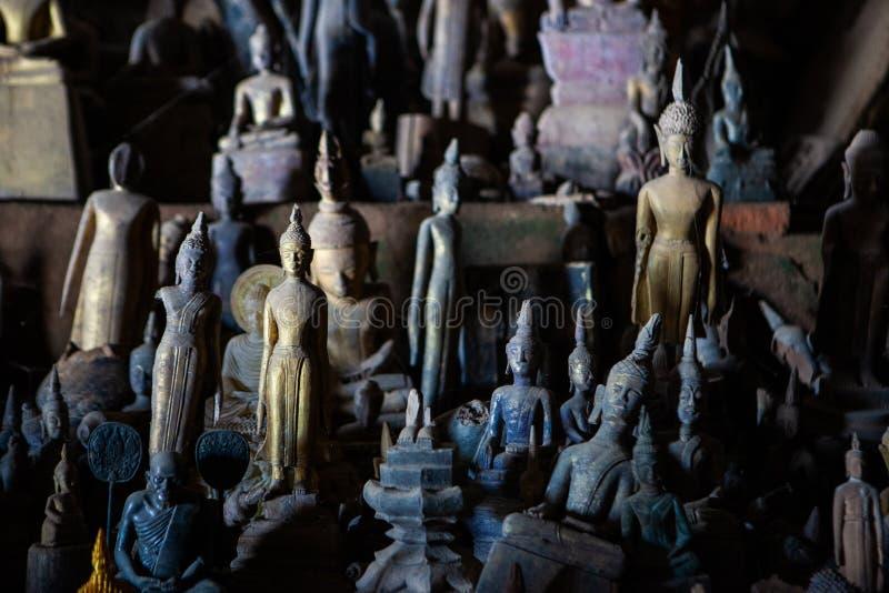 De oude verlaten standbeelden van Boedha die met stof en spinneweb in Pak Ou worden behandeld holt binnen Luang Prabang, Laos uit stock foto's