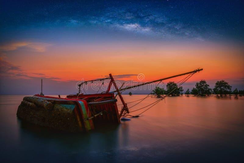 De oude vissersboot kapseiste op overzees met melkachtige binnen manier bij zonsondergang royalty-vrije stock afbeeldingen