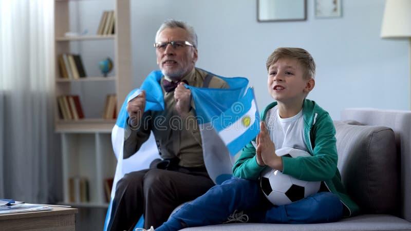 De oude vlag van Argentinië van de mensenholding, het letten op voetbal met jongen, die zich over spel ongerust maken royalty-vrije stock fotografie