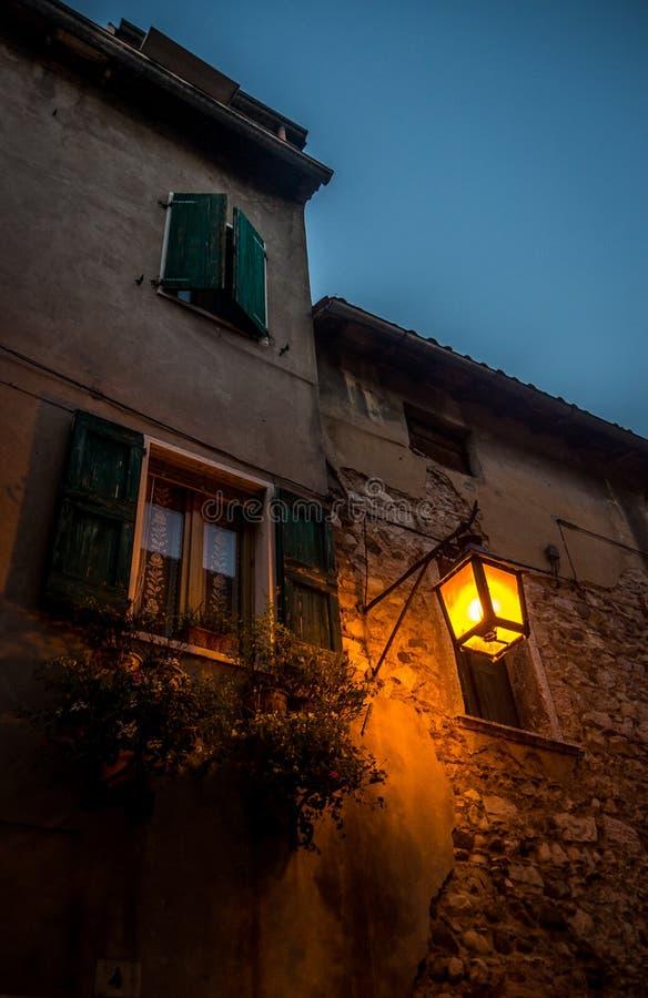 De oude voorgevel van een huis met blinden en straatlantaarn in kleine Italiaanse stad royalty-vrije stock foto's