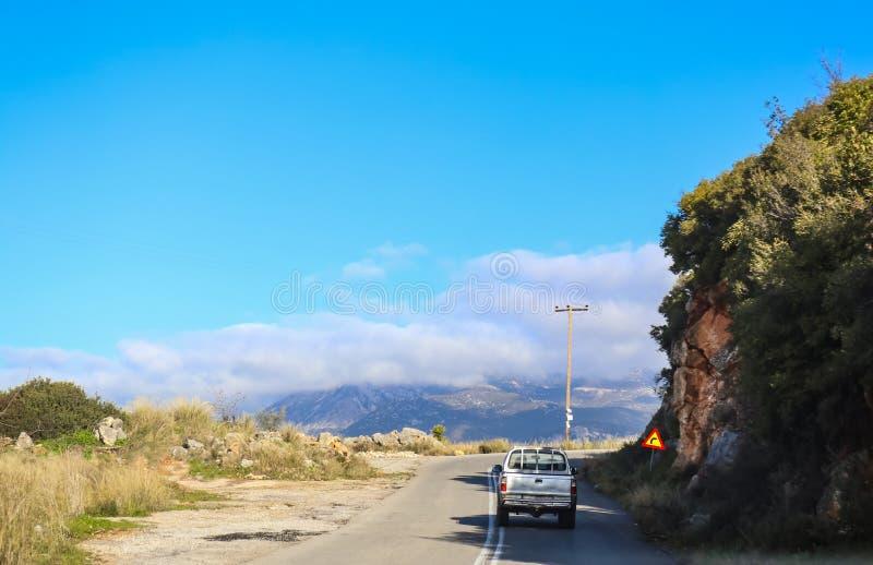De oude vrachtwagen die extreme kromme op twee steegweg naderen in de bergen met mist bedekte mountian waaier in de afstand stock fotografie