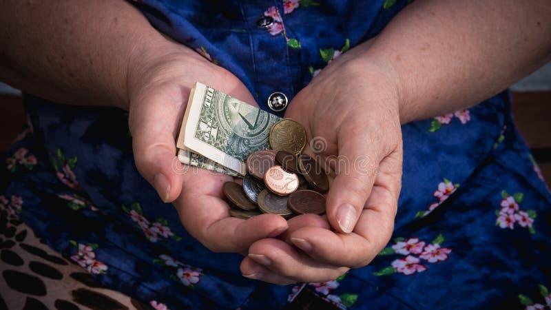 De oude vrouw bedelt voor aalmoes Close-up van geld en muntstukken ter beschikking van slechte vrouw stock afbeeldingen