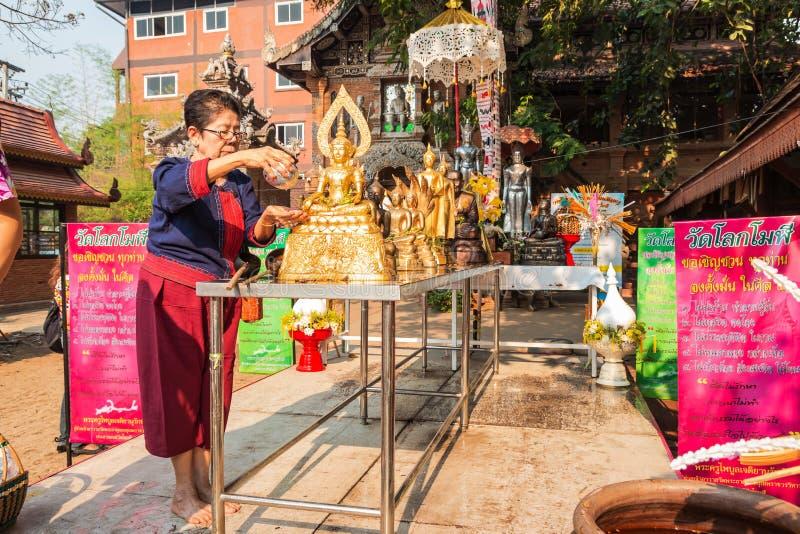 De oude vrouw bestrooit water op een Standbeeld van Boedha royalty-vrije stock foto