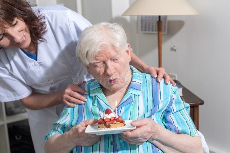 De oude vrouw blaast uit een kaars van de verjaardagscake stock fotografie