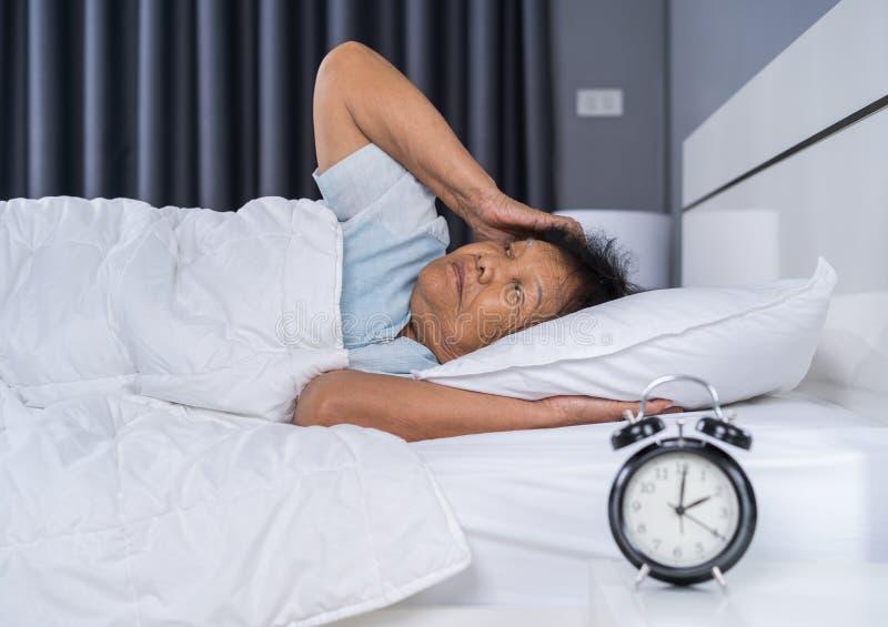 De oude vrouw die aan slapeloosheid lijden probeert aan slaap in bed stock afbeelding