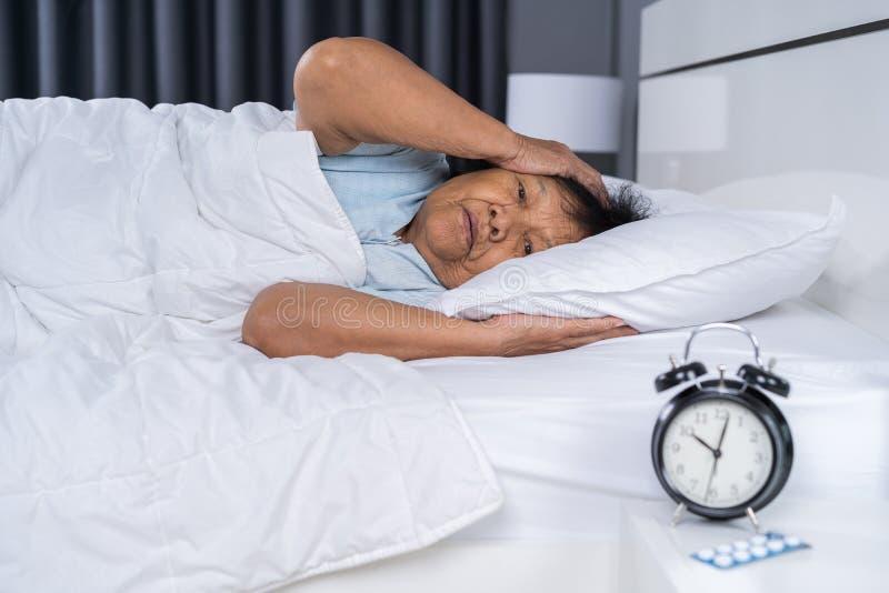 De oude vrouw die aan slapeloosheid lijden probeert aan slaap in bed stock afbeeldingen