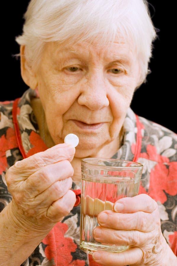 De oude vrouw drinkt een tablet royalty-vrije stock afbeelding
