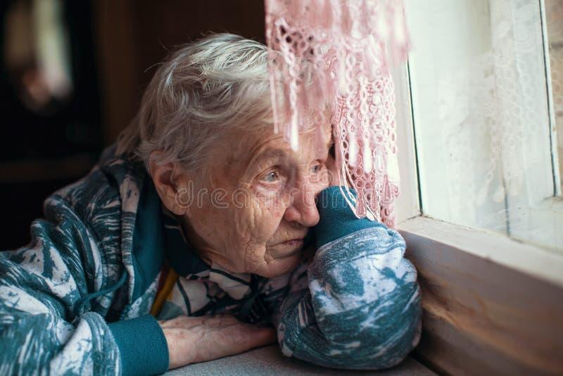 De oude vrouw is droevige emoties het huis eenzaamheid stock foto